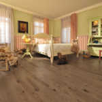 Cute Girl Bedroom featuring Teddy Bear color hardwood floor (Sweet Memories Series-Handcrafted Oak)For more information, visit www.miragefloors.comFurnitures coming from La Galerie du Meuble Coastal Living Bed Coastal Living Cabinet Round Table Desk ChairFurnitures coming from La Vieille Armoire Rocking Chair Lamp, Bedding, curtains and accessories